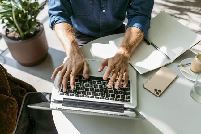 Empresario usando portátil en la mesa en la cafetería - foto de stock