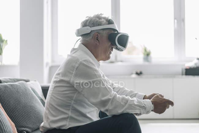 Uomo d'affari che gioca al videogioco con occhiali di realtà virtuale mentre si siede sul divano in ufficio — Foto stock