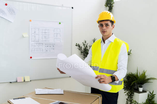 Confident young male engineer holding blueprint at office — Stock Photo