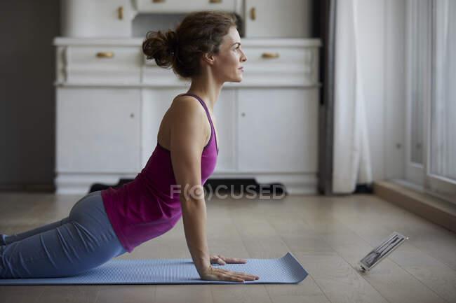 Женщина, использующая цифровой планшет во время занятий йогой дома — стоковое фото