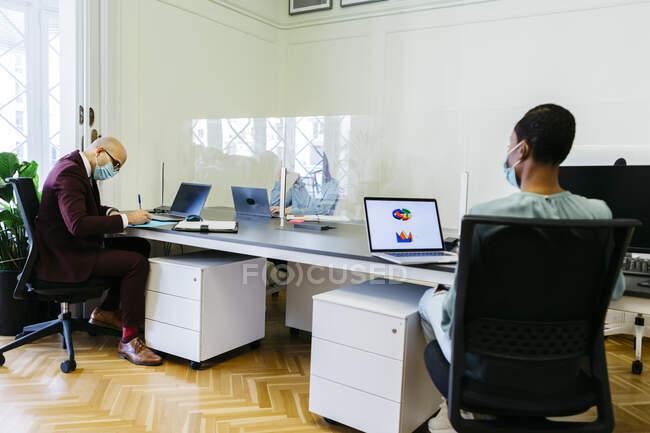 Berufstätige mit Schutzmaske arbeiten am Schreibtisch im Büro — Stockfoto