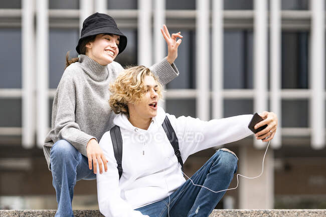 Hombre rubio tomando selfie mientras amiga haciendo señal de paz - foto de stock