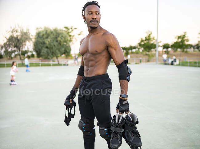 Безсоромний спортсмен, який тримає черевик з роликами, стоячи на землі. — стокове фото