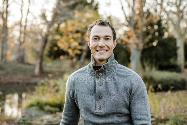 Smiling handsome man sitting in public park — Stock Photo