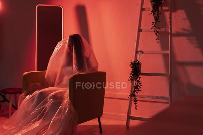 Mujer sentada en sillón cubierto de plástico en casa durante la pandemia - foto de stock