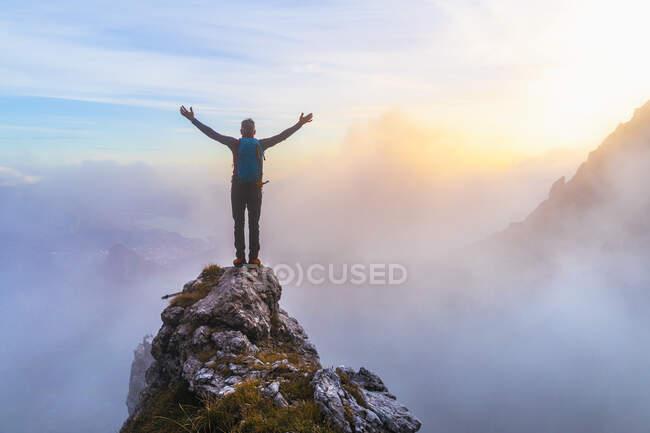 Senderista masculino pensativo con los brazos extendidos de pie en el pico de la montaña durante el amanecer en los Alpes bergamascos, Italia - foto de stock