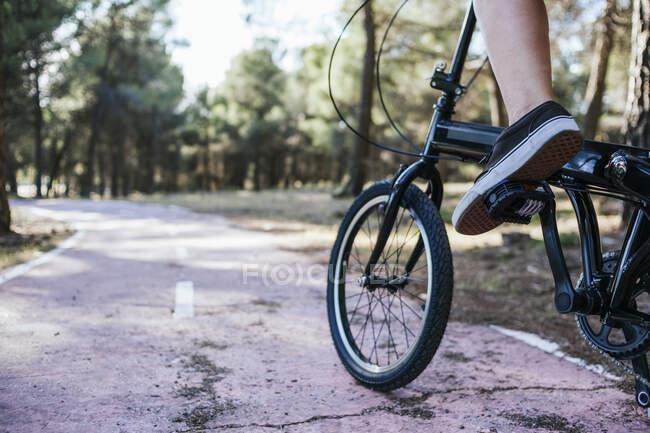 Donna in bicicletta su strada in campagna — Foto stock
