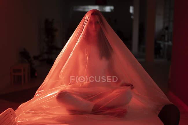 Mujer joven cubierta de plástico sentada con las piernas cruzadas en la mesa durante la crisis del coronavirus - foto de stock