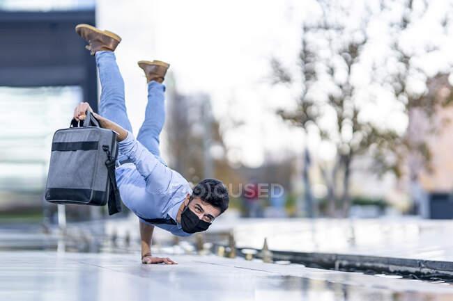 Людина в масці, тримаючи портфель під час роботи на стежці під час Ковід-19 — стокове фото