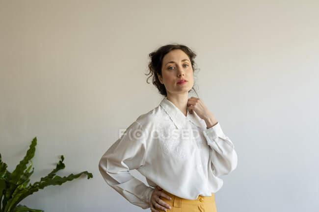 Modelo feminino bonito com a mão no quadril vestindo roupas estilo retro em pé contra a parede — Fotografia de Stock