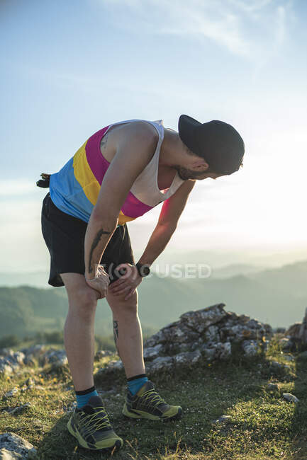Atleta cansado con la mano sobre la rodilla mirando a la vista mientras está de pie en la montaña - foto de stock