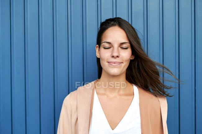 Задумчивая женщина с закрытыми глазами, стоящая напротив голубой металлической стены — стоковое фото