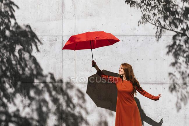 Mujer pelirroja sonriente sosteniendo el paraguas mientras está de pie contra la pared de sombra del árbol - foto de stock