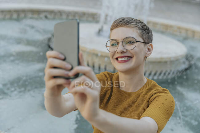 Sonriente mujer adulta medio tomando selfie en el teléfono inteligente de pie contra la fuente - foto de stock