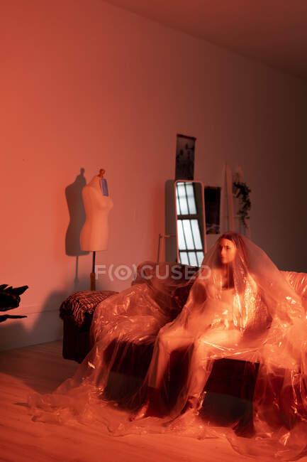 Mujer joven y preocupada cubierta de plástico sentada en el sofá en casa durante COVID-19 - foto de stock