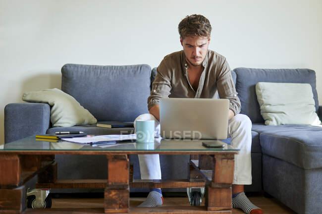 Бизнесмен концентрируется во время работы над ноутбуком дома — стоковое фото