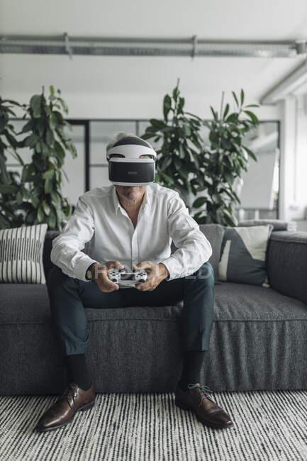 Uomo d'affari che utilizza la realtà virtuale durante la riproduzione di videogiochi in ufficio — Foto stock