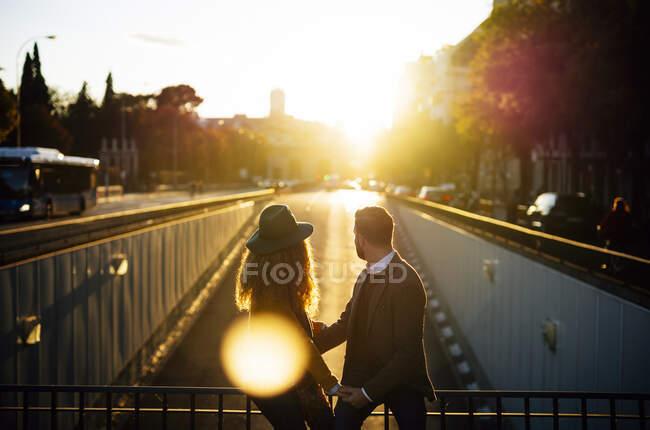 Пара смотрит в сторону, сидя на мосту перила вместе в городе во время заката — стоковое фото