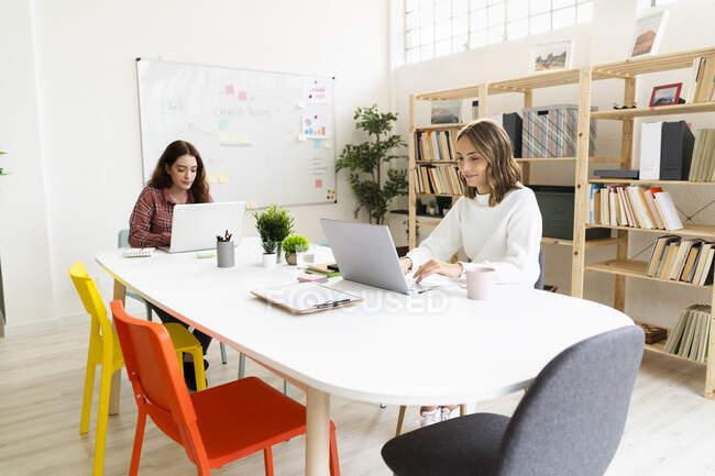 Молоді жінки працюють на ноутбуці, сидячи за столом у офісі. — стокове фото
