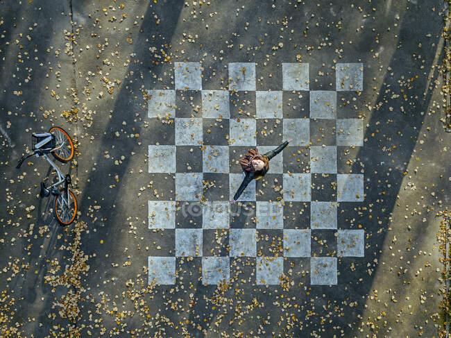 Mujer con los brazos extendidos girando sobre asfalto pintado con patrón de tablero de ajedrez - foto de stock