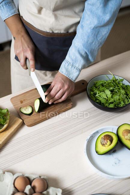 Sección media de mujer rebanando pepino en la tabla de cortar - foto de stock