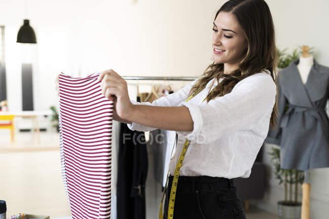 Sastre femenino creativo sosteniendo tela a rayas mientras está de pie en el estudio - foto de stock