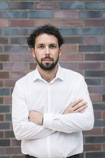 Male entrepreneur with arms crossed against wall — Stock Photo