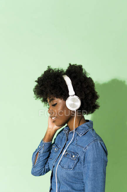 Young woman wearing headphones standing against green background — Stock Photo