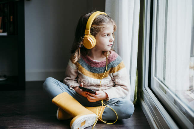 Girl wearing headphones using mobile phone while sitting by window at home — Stock Photo