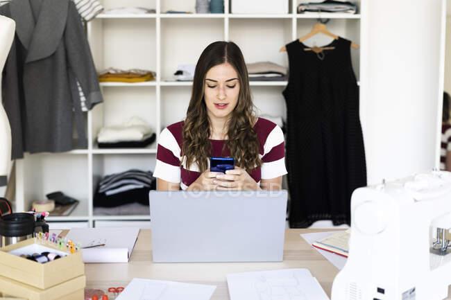 Diseñadora de moda femenina usando un teléfono inteligente mientras está sentada con un portátil en el estudio - foto de stock