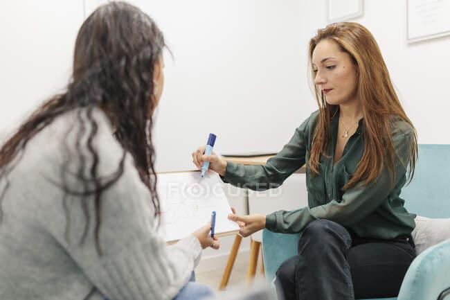 Psicólogo explicando carta con bloc de notas mientras está sentado por paciente en el consultorio — Stock Photo