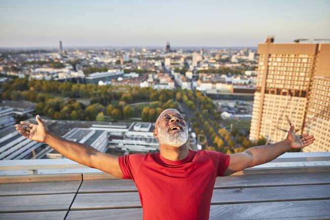 Felice uomo barbuto con le braccia distese appoggiate indietro mentre in piedi sulla terrazza edificio in città durante il tramonto — Foto stock