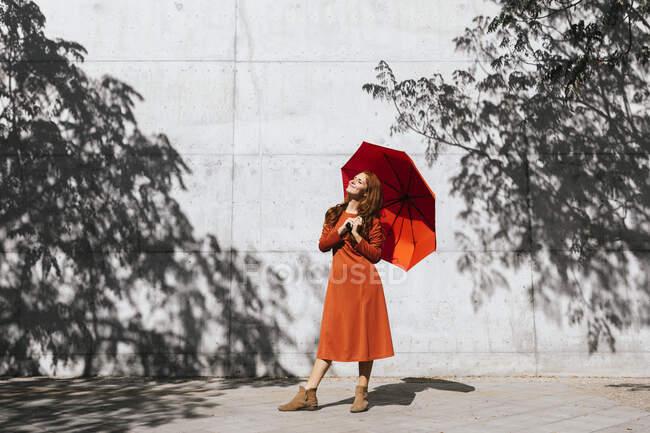Mujer sonriente sosteniendo el paraguas mientras está de pie contra la pared de sombra del árbol - foto de stock