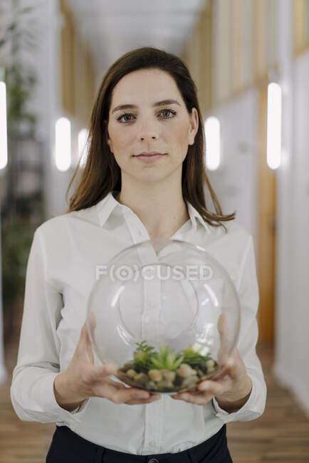 Mujer sosteniendo la olla de terrario en la mano mientras está de pie en la oficina - foto de stock