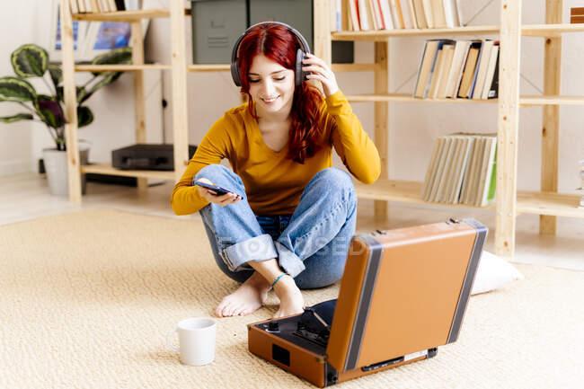Lächelnde rothaarige Frau mit Kopfhörer und Handy, während sie zu Hause am Plattenteller sitzt — Stockfoto