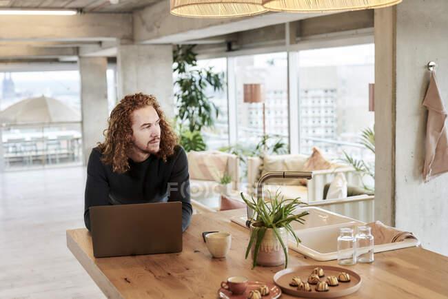 Нечемний чоловік, що відвернувся, покладаючись на стіл удома. — стокове фото