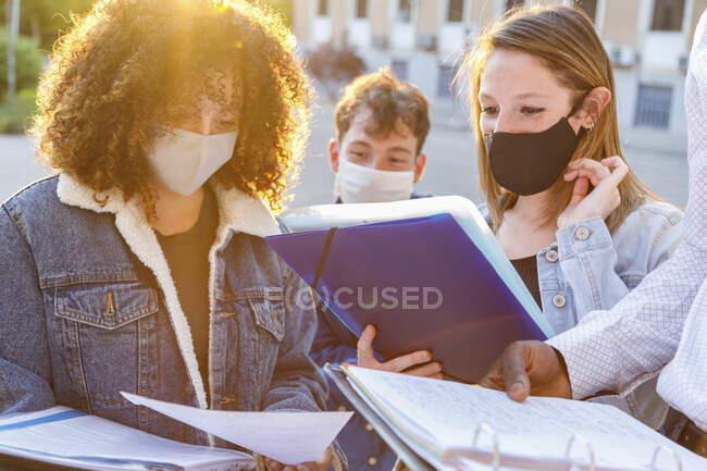 Чоловіки і жінки в захисній масці обговорюють нотатки в університетському містечку. — стокове фото