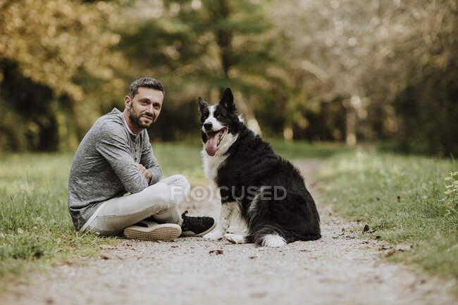 Hombre y perro sonrientes sentados en el sendero del parque público - foto de stock