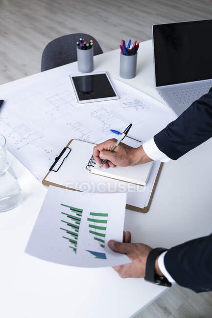 Hands of male entrepreneur analyzing growth graph while writing in diary at creative workplace — Stock Photo