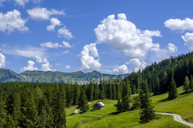 Vista panorámica de las nubes sobre la cabaña solitaria en los Alpes bávaros durante el verano - foto de stock
