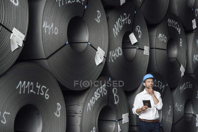 Empresario masculino con la mano en la barbilla que sostiene la tableta digital mientras está parado contra los rollos de acero en fábrica - foto de stock