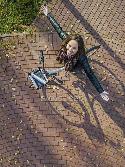 Retrato aéreo de una joven de pie sobre la bicicleta y sonriendo a la cámara con los brazos levantados - foto de stock