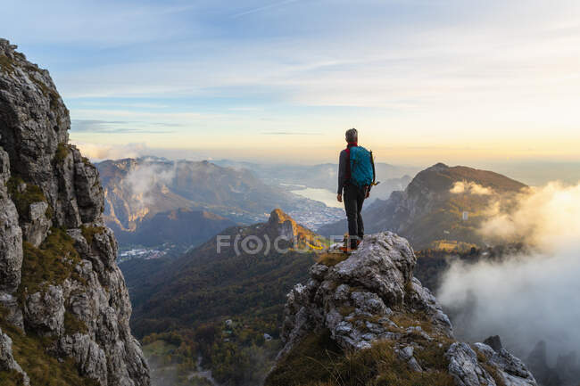Pensive hiker looking at view while standing on mountain peak during sunrise at Bergamasque Alps, Italy — Stock Photo