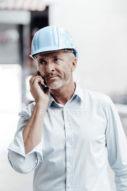 Male engineer in hardhat looking away while talking on smart phone in industry — Stock Photo