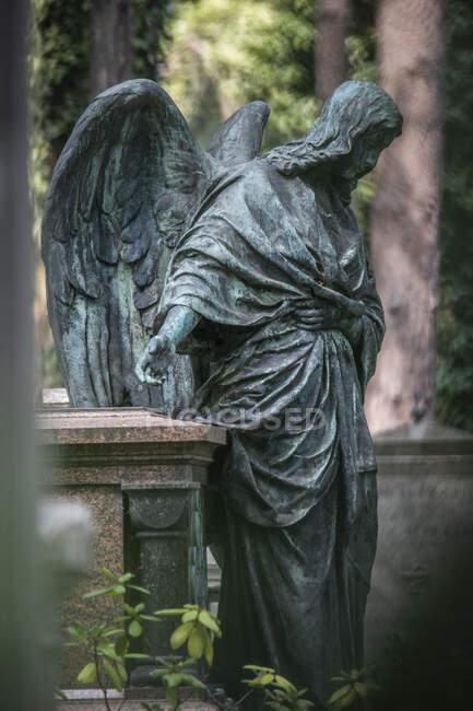 Estátua de anjo de pé ao lado do túmulo no cemitério — Fotografia de Stock