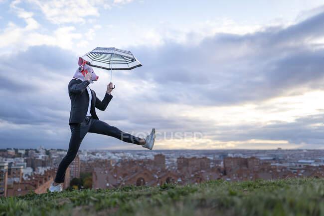 Бізнесмен у масці свині та бездротові навушники, які розмовляють по телефону проти неба. — стокове фото