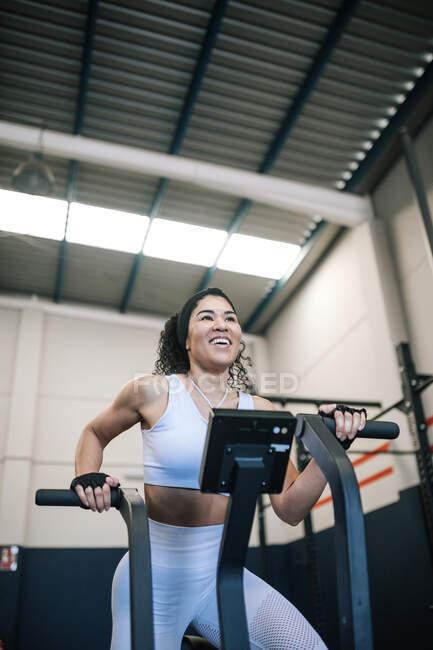 Happy sportswoman training on exercise bike in gym — стоковое фото