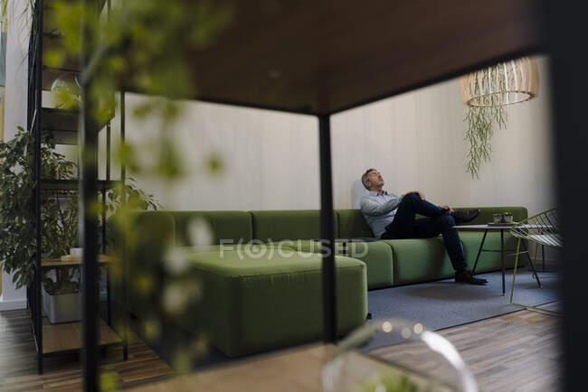 Бізнесмен відпочиває, сидячи на дивані в офісі. — стокове фото