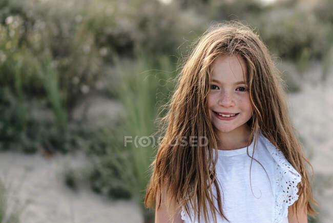 Девушка с каштановыми волосами стоит на пляже в солнечный день — стоковое фото