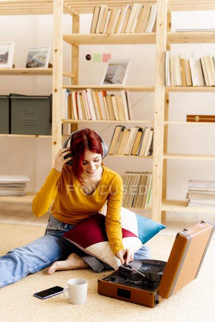 Lächelnde Frau trägt Kopfhörer, während sie Plattenspieler zu Hause benutzt — Stockfoto